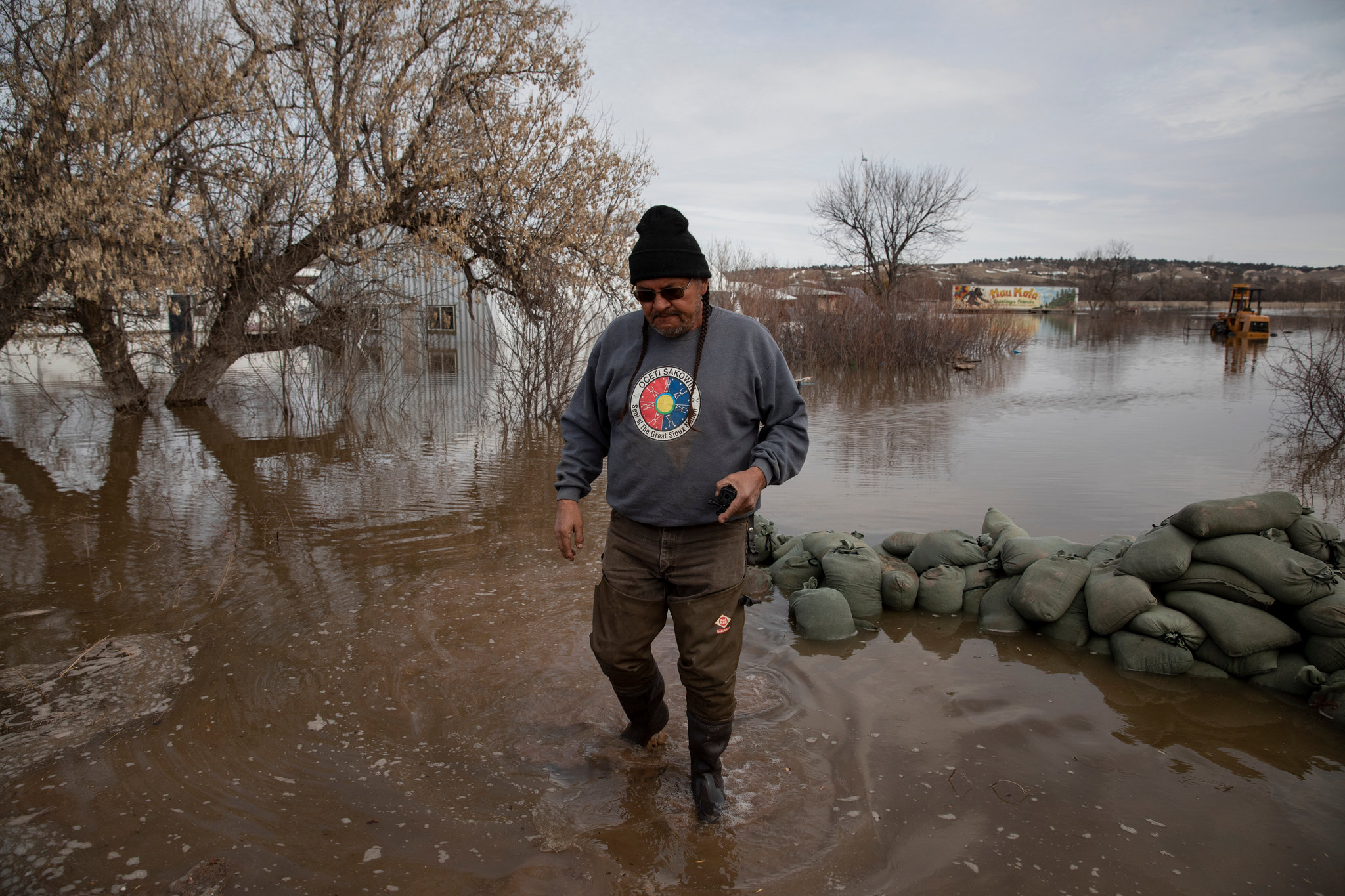 The rising floodwaters stopped just sort of the home where Henry Red Cloud and his family rode out the storm, but other buildings on their property including their solar power business were inundated. Credit: Kristina Barker for The New York Times