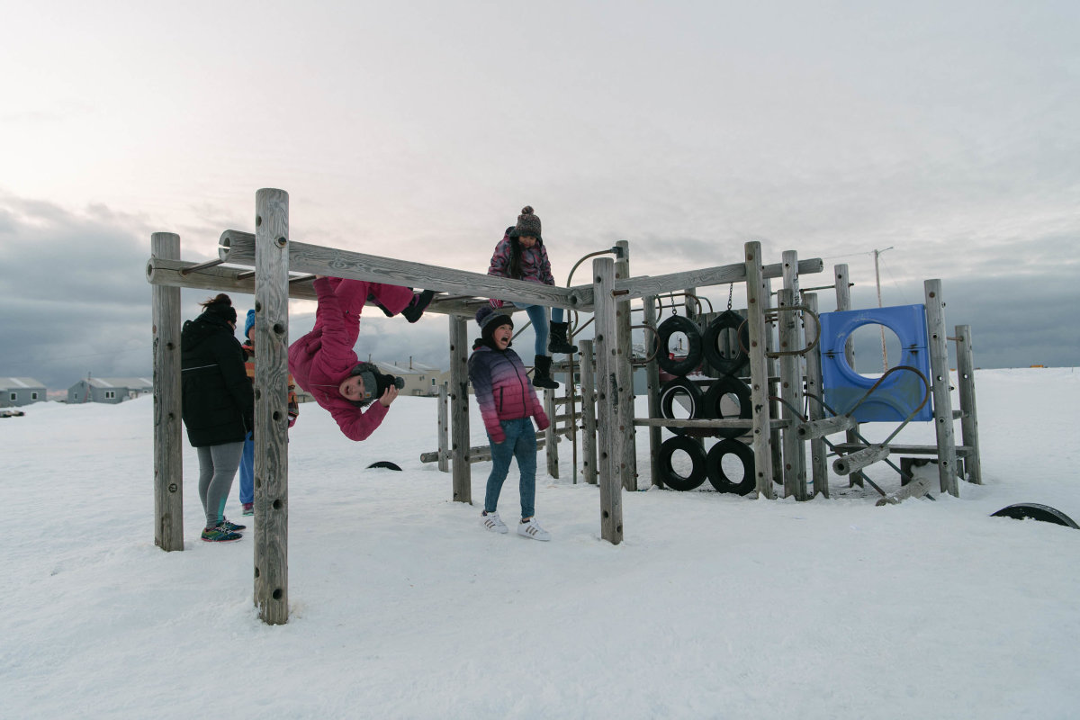 Kids play on a snowy playground in the light of Arctic spring. With each new generation, the traumas experienced by previous generations grow more distant, though the community's youth will undoubtedly face new challenges as they come of age. (Photo: Kiliii Yüyan)