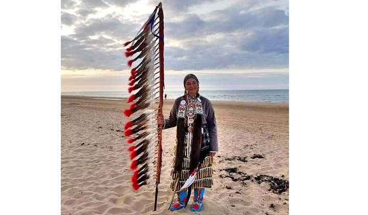 Command Sergeant Major Julia Kelly (U.S. Army retired), one of 80 Native American delegates to the 75th anniversary observance of D-Day, stands on Omaha Beach. Kelly holds an eagle feather staff, an American Indian symbol of respect, honor, and patriotism. (Courtesy of Julia Kelly)