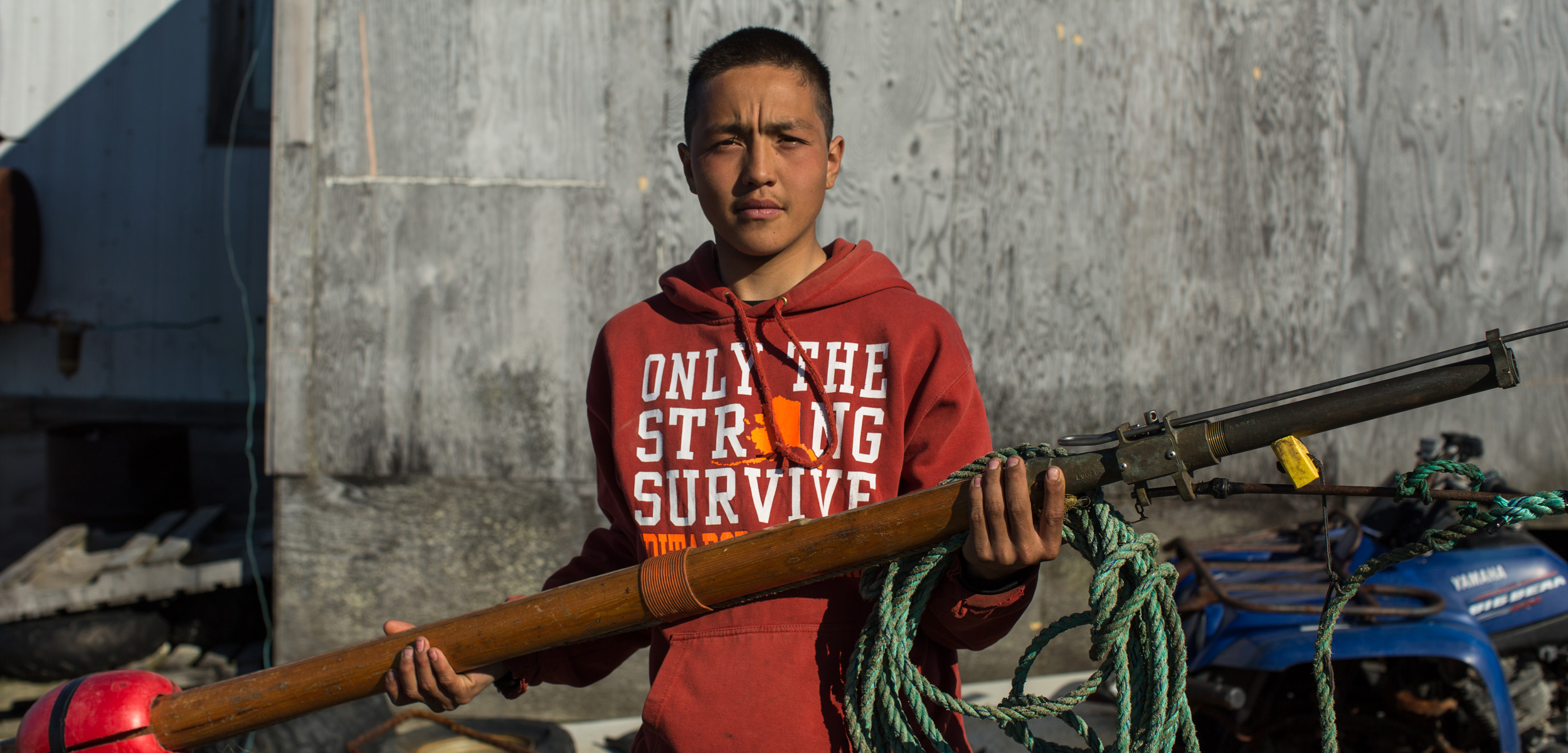 Chris Apassingok, 16, holds the darting gun he used to harpoon a whale this spring outside his family's home in Gambell, Alaska.    Ash Adams