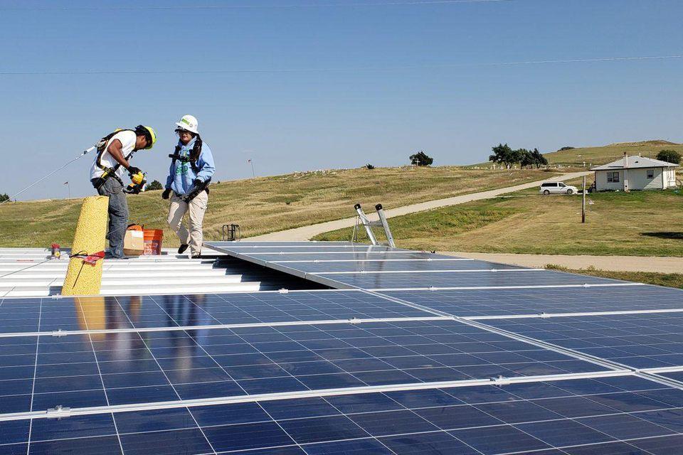 Tribal members install solar panels on the Okreek community building on the Rosebud Indian Reservation. GRID ALTERNATIVES