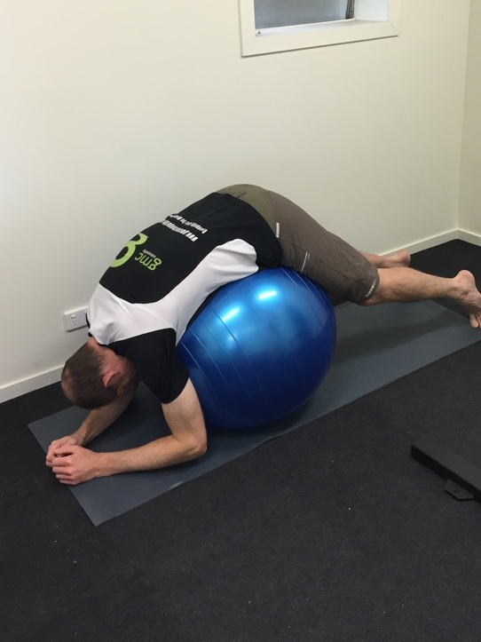 "I couldn't find a picture of someone doing this is bed, but the plan from last visit was to use the foam roll and several pillows to get a similar effect as you see in the picture. The ball could be used, but I want more of a fulcrum at the low back, not at the hips (Hips bend find, that is whey the ""touch your toes"" activity can be done, because you are not bending the low back). I would try for a 10 minute stretch daily at least, if not twice per day. Just a gentle stretch, no ""pain pain""."