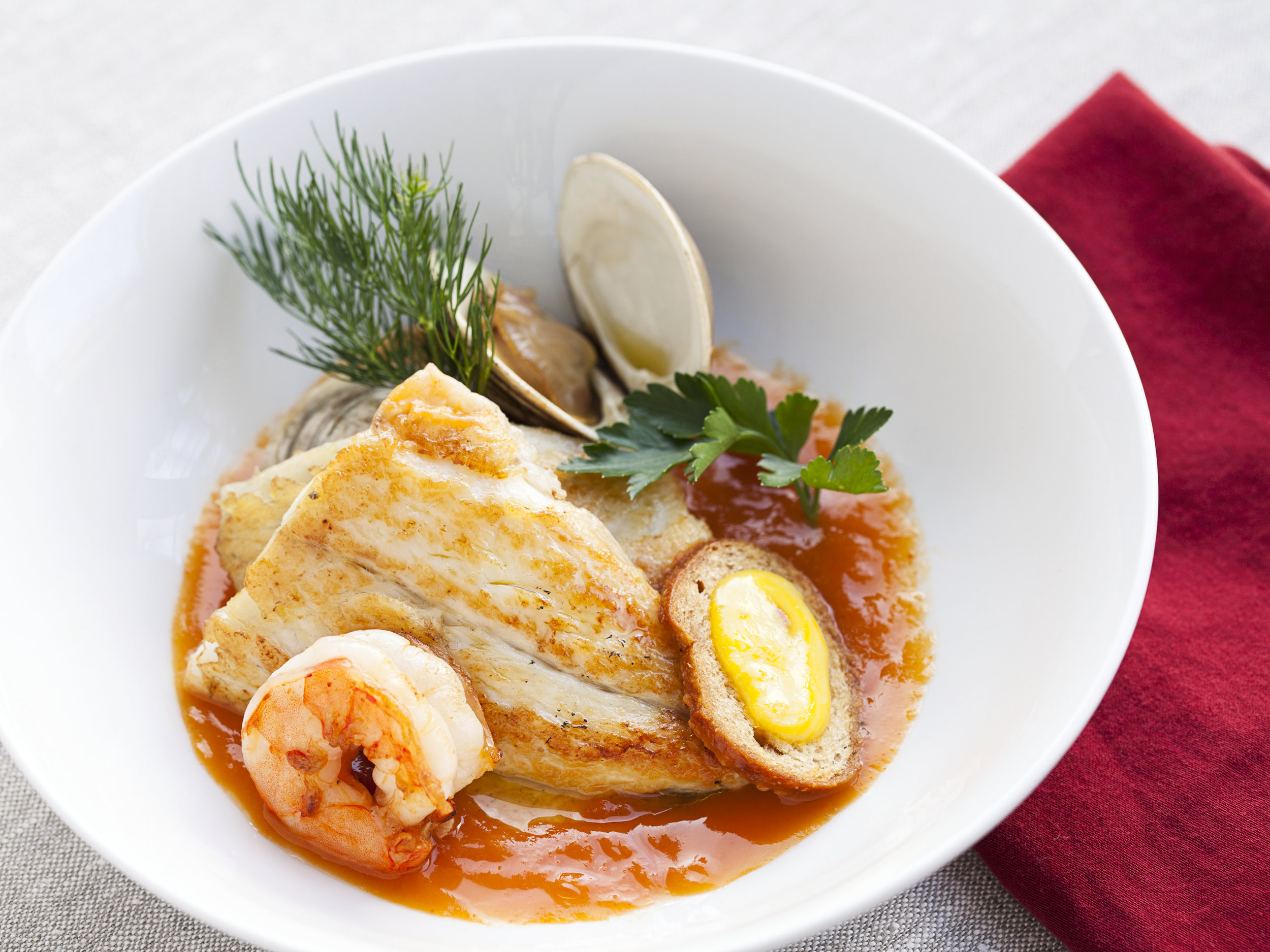 Branzino with bouillabaisse sauce, t clams, seared shrimp, and saffron crouton.jpg