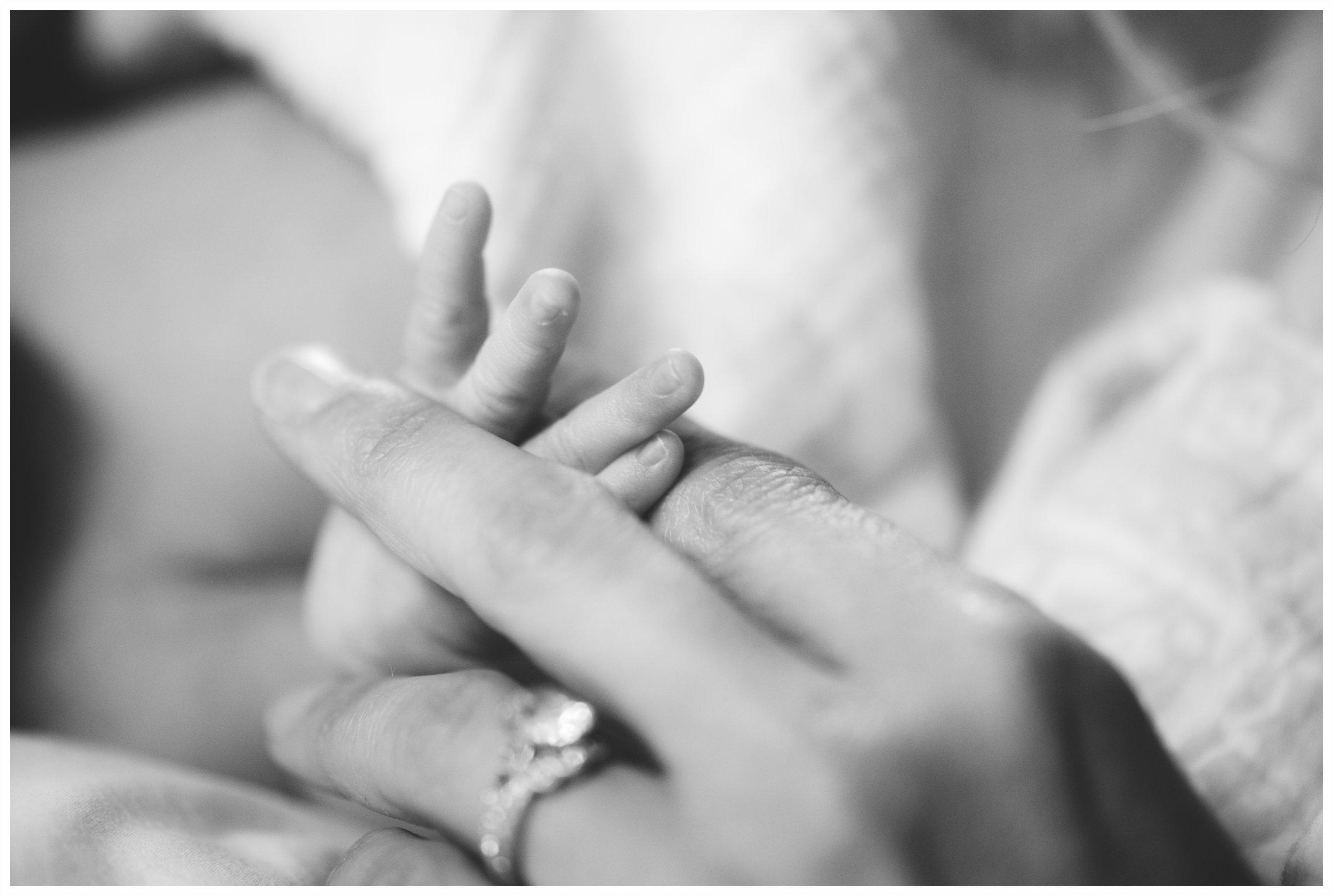 mother holding newborn fingers