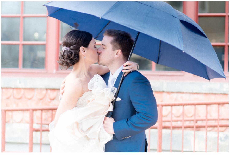 brida and groom kissing under umbrella