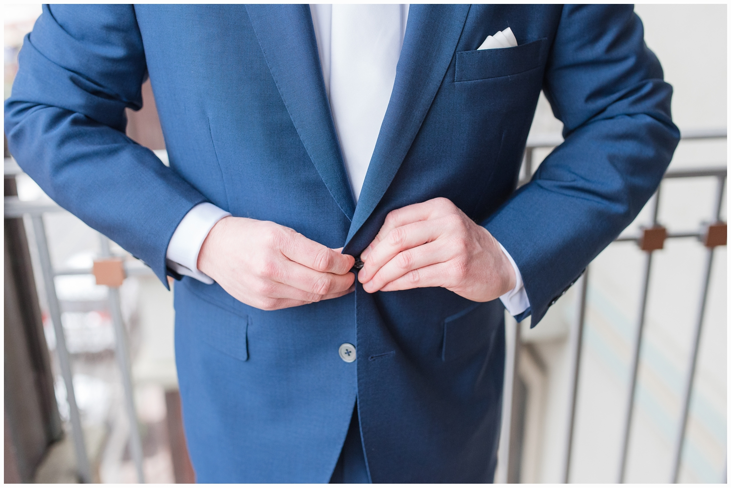 groom buttoning his suit
