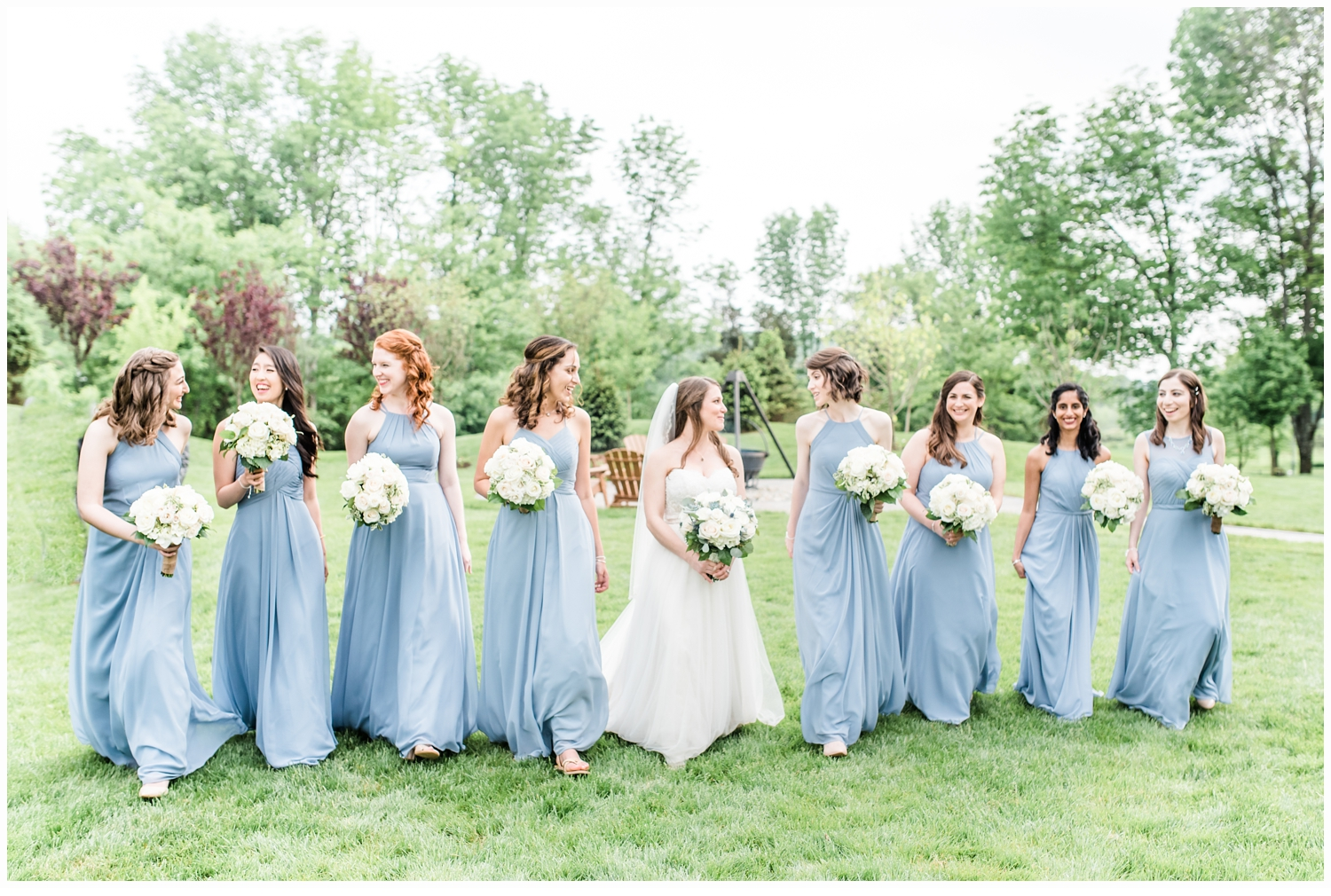 bride and bridesmaids walking in field