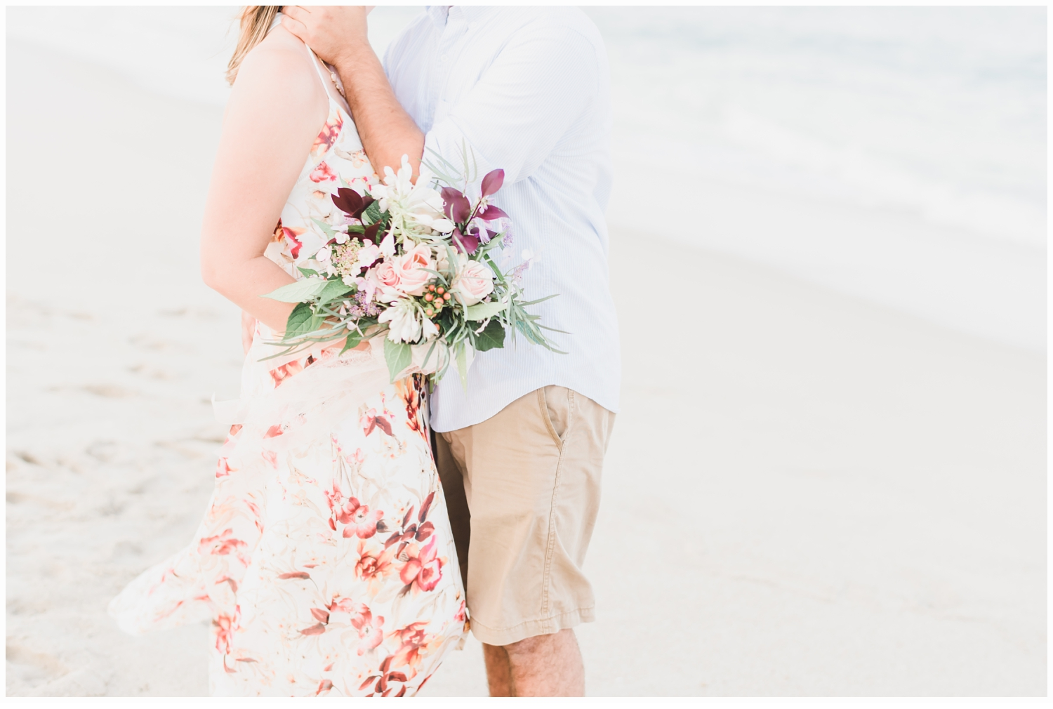 couple on a beach with a floral bouquet