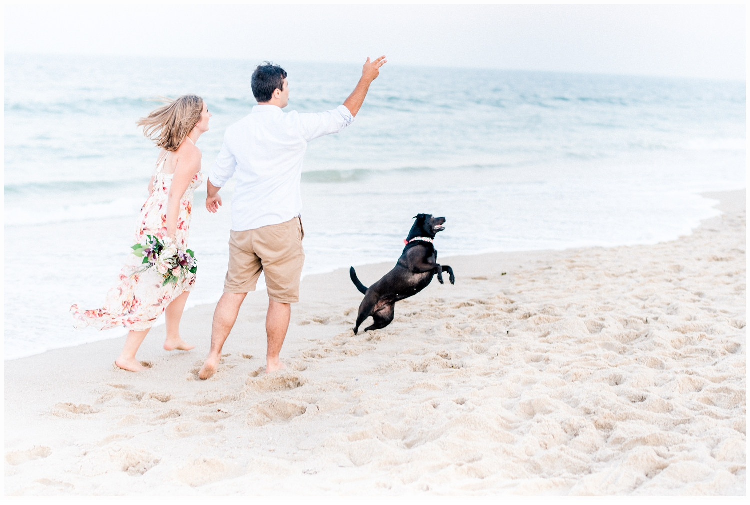 couple playing on beach with dog