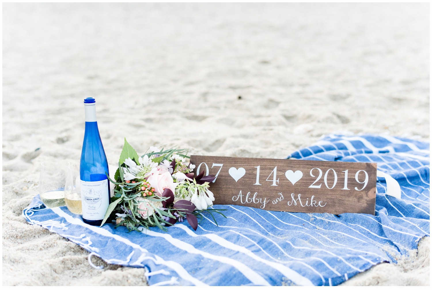 bottle of wine on a beach blanket
