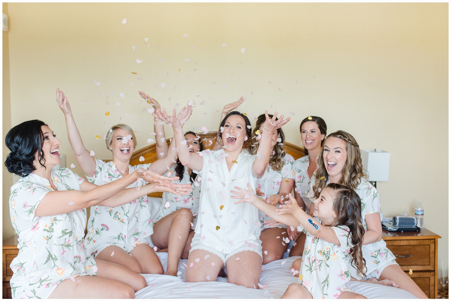 bride and bridesmaids throwing confetti on bed
