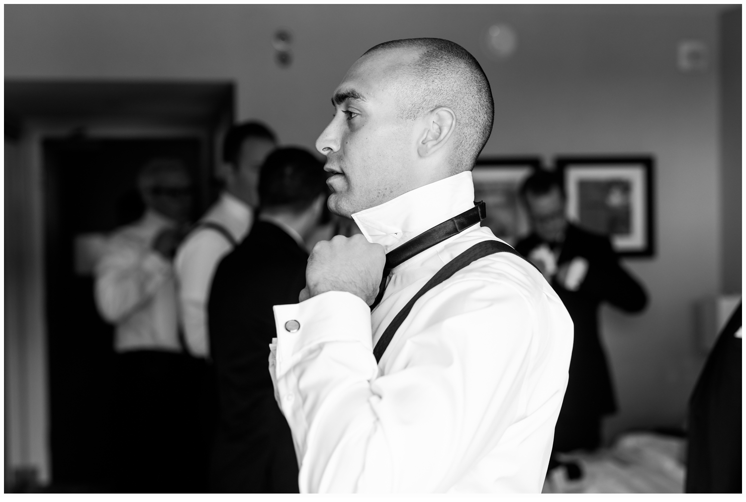 groom putting on his bow tie