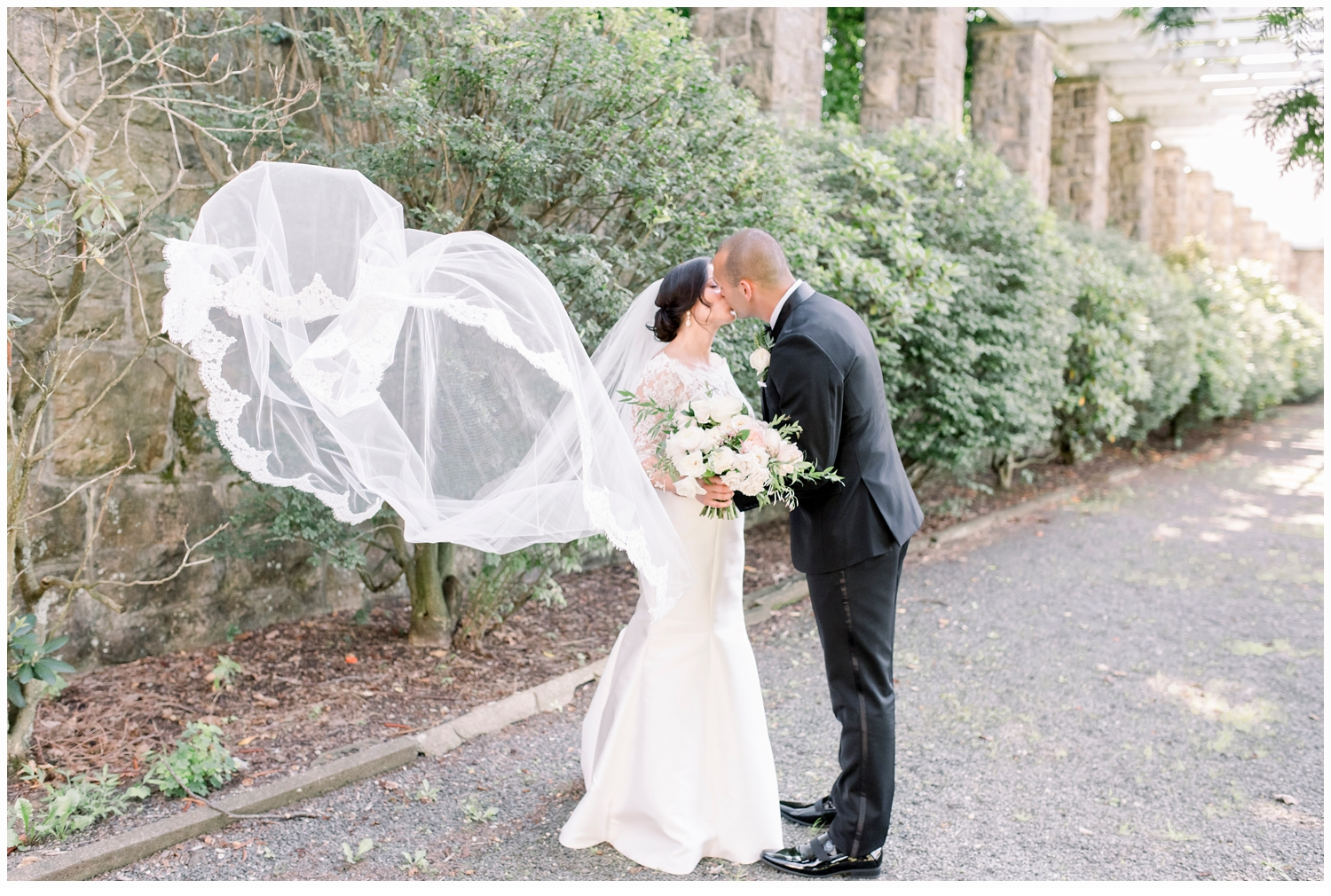 bride and groom portrait with veil blowing in the wind