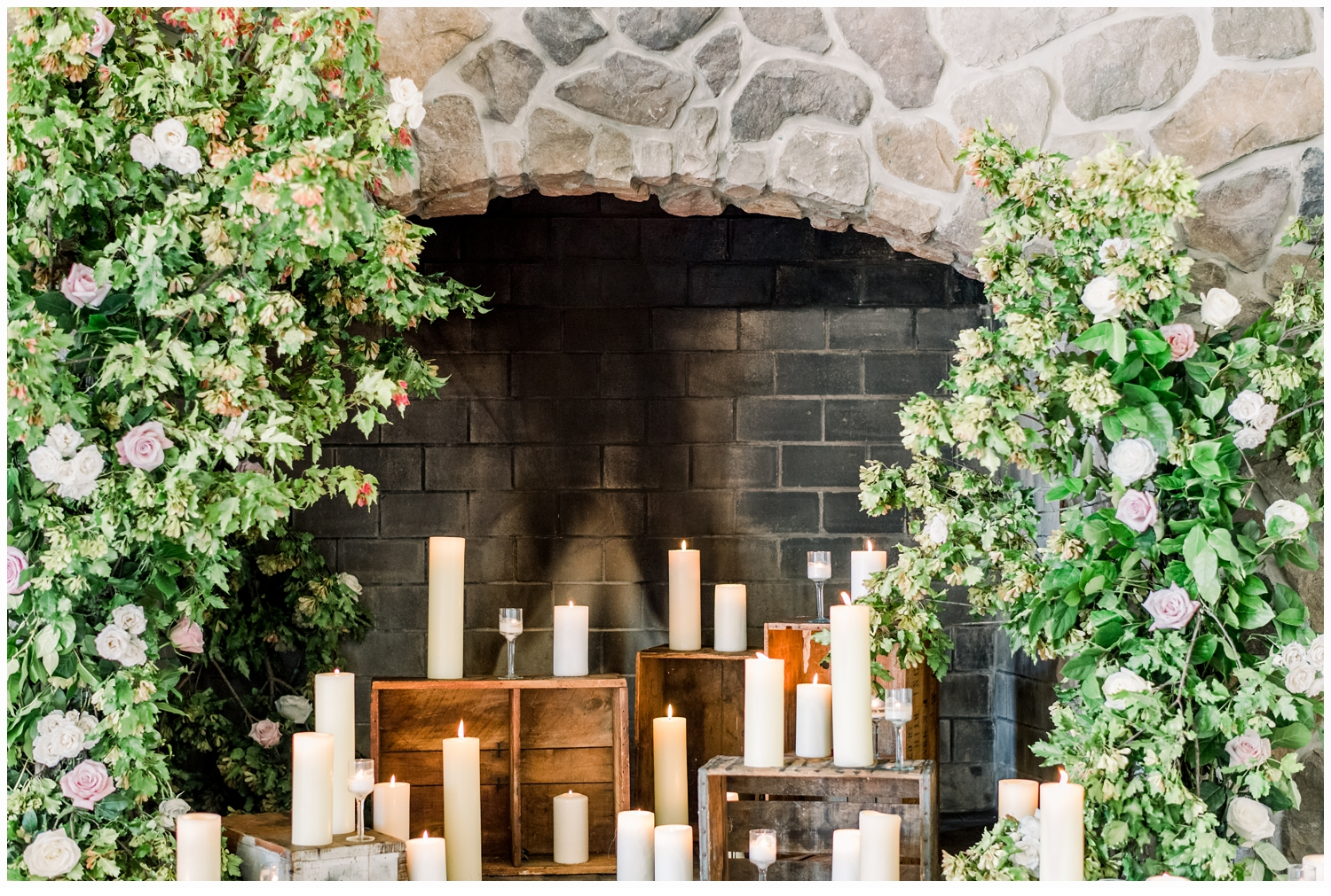 green florals and candles on a fireplace
