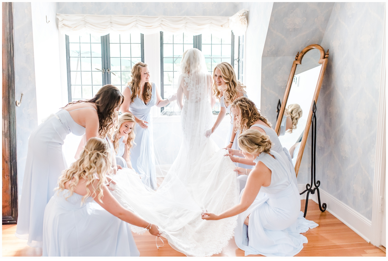 bridesmaids helping bride put on dress