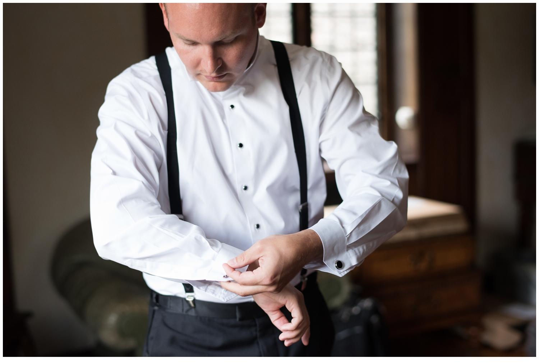 groom putting on cufflinks on wedding day