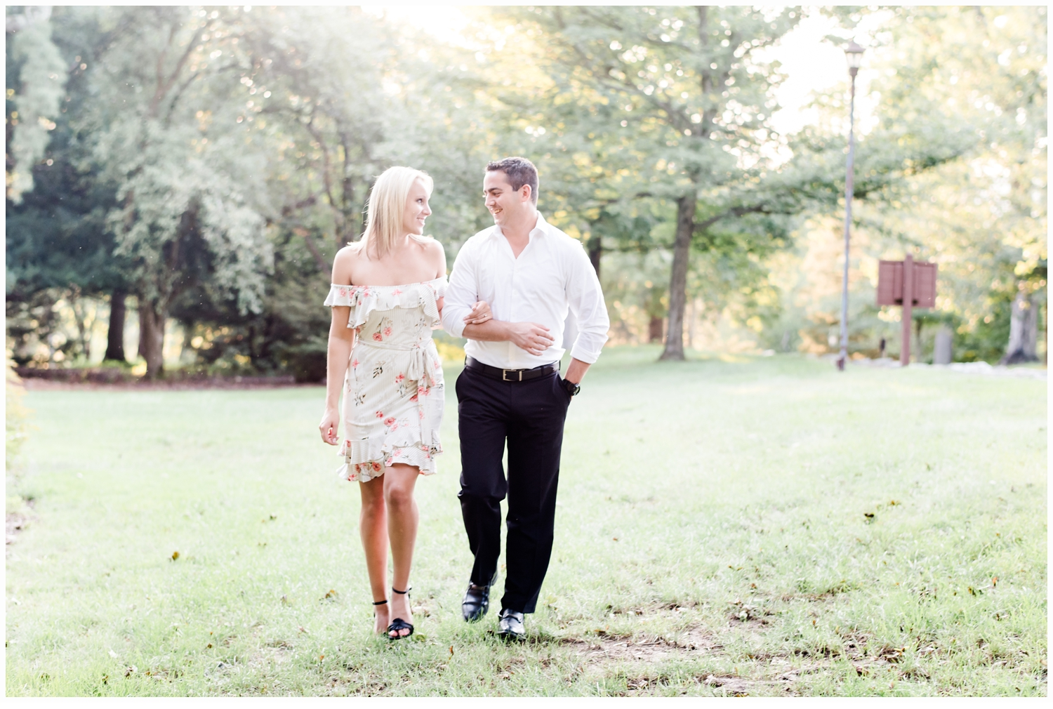 engaged couple walking in park