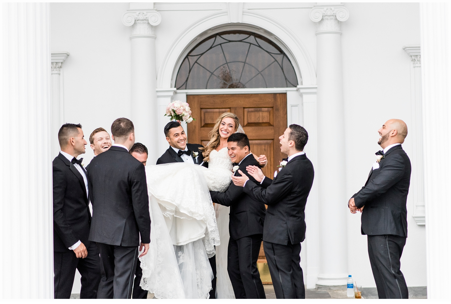 groomsmen lifting bride up in the air