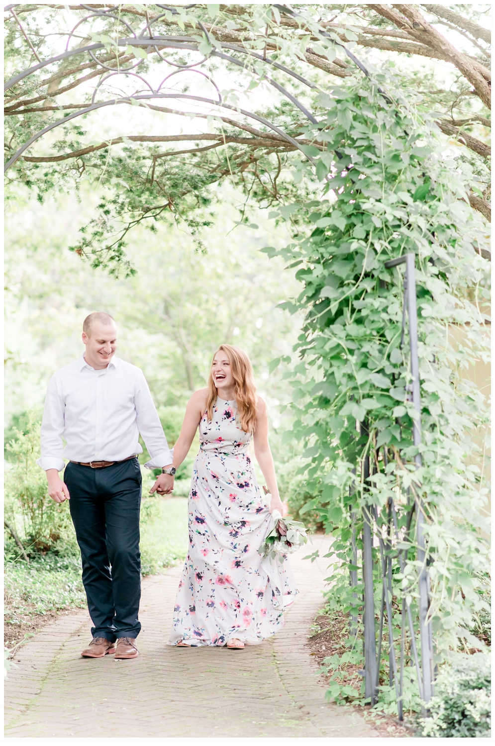 man and woman holding hands walking in garden