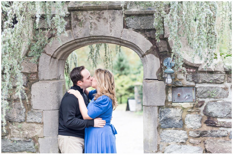 a couple kissing under a bridge
