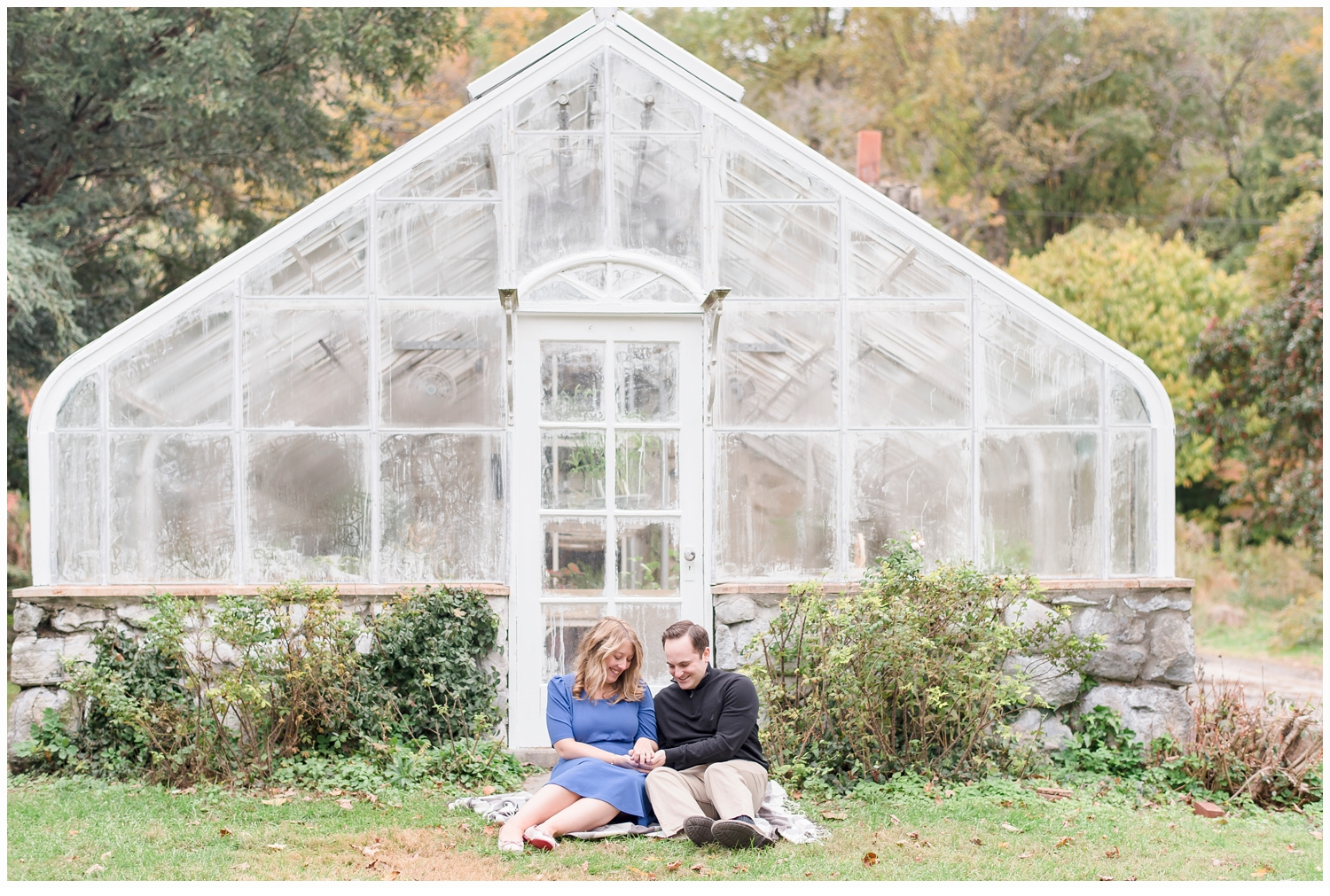 a couple sitting in front of a pretty green house
