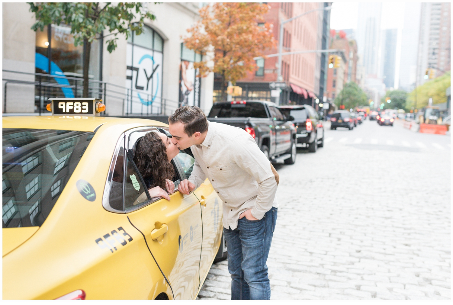 engaged couple kissing in yellow cab in nyc
