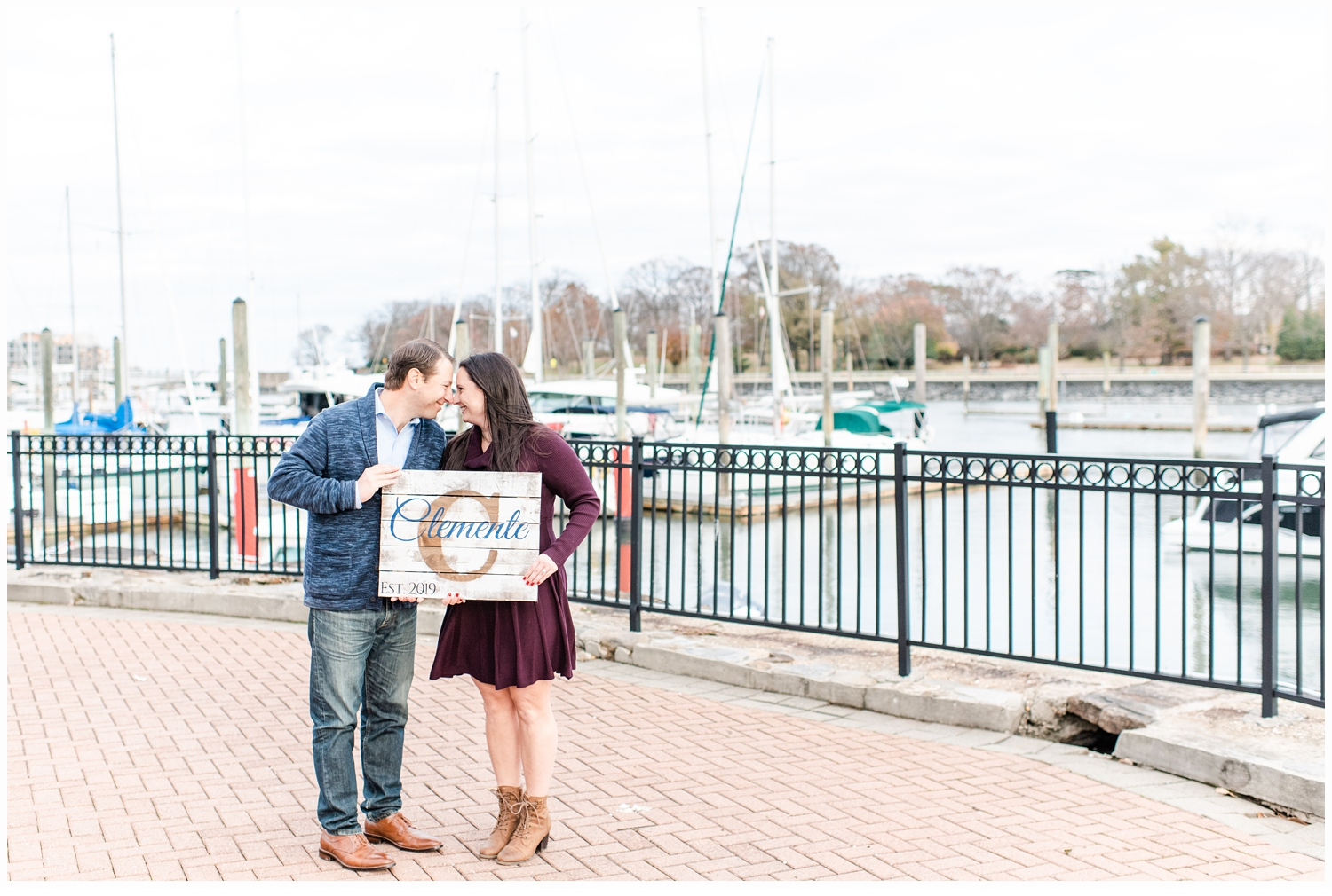 engaged couple holding a sign