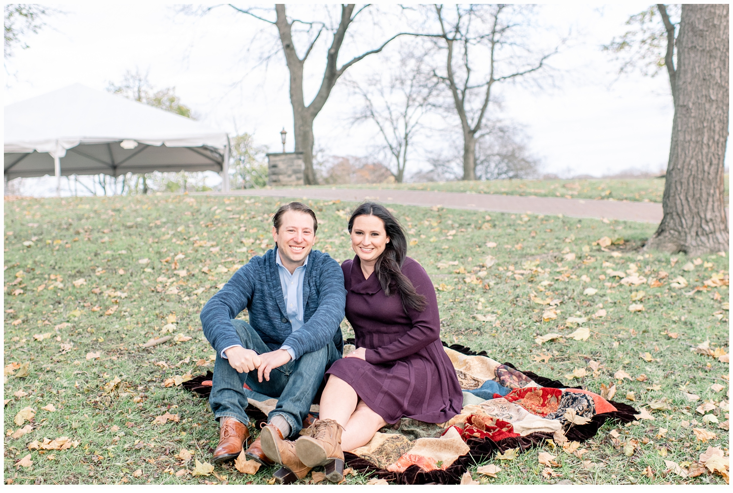 engaged couple sitting on a blanket in the grass