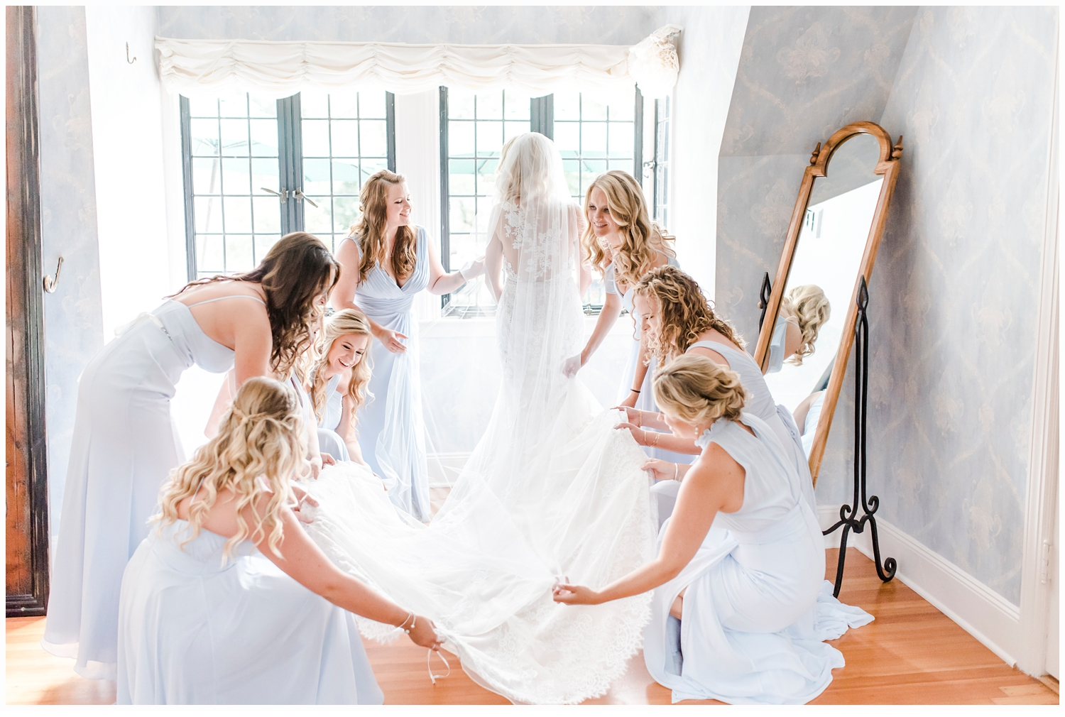 bridesmaids helping bride put on wedding gown