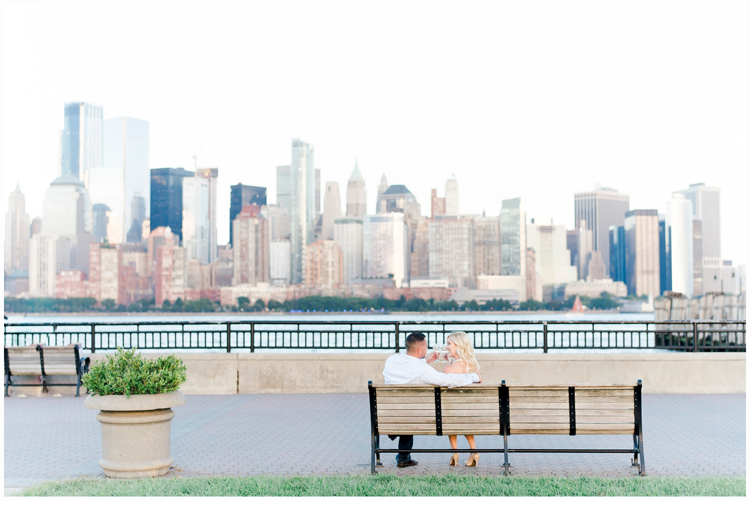 engaged couple sitting on bench at liberty state park