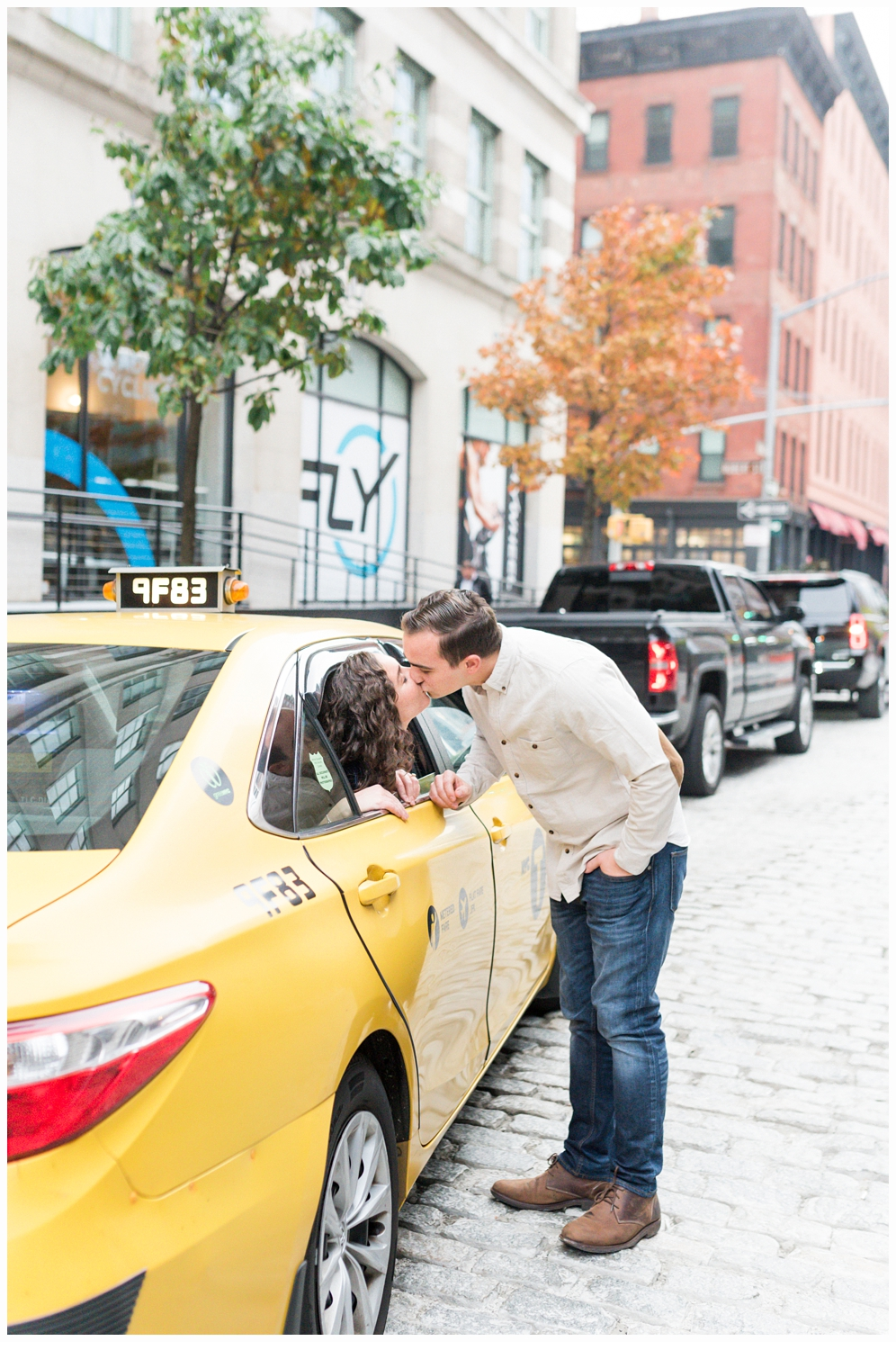 engaged couple kissing in yellow nyc cab
