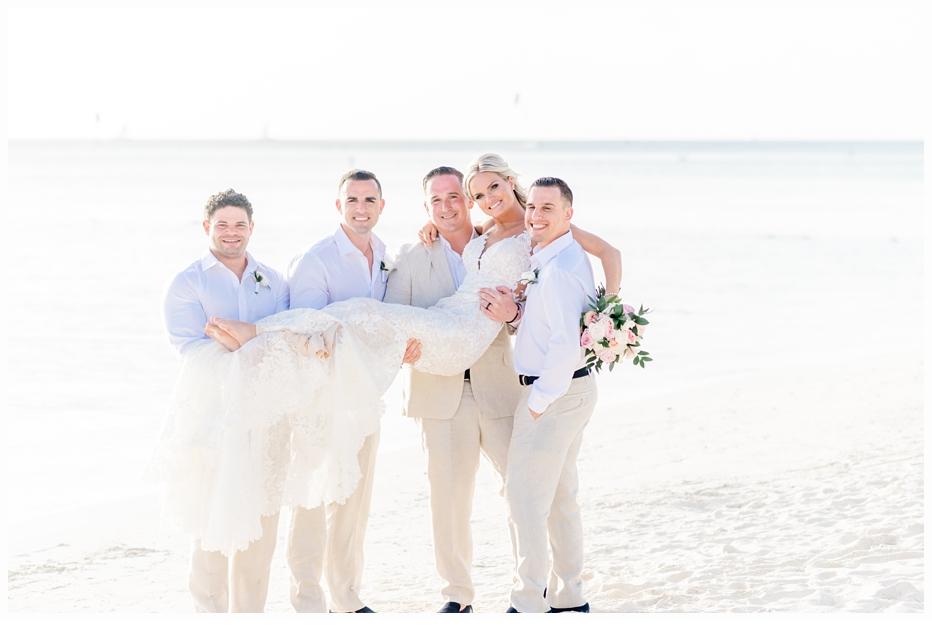 groom and groomsmen holding bride