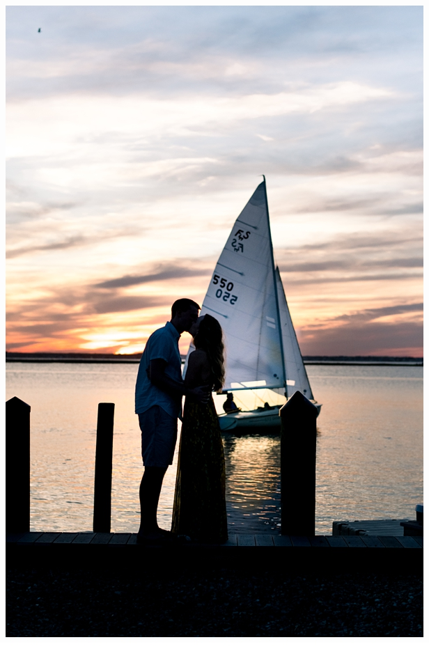 sunset image of a couple kissing with a sailboat in the background