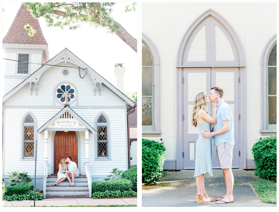 engaged couple sitting on the steps of a pretty blue chapel sharing a kiss