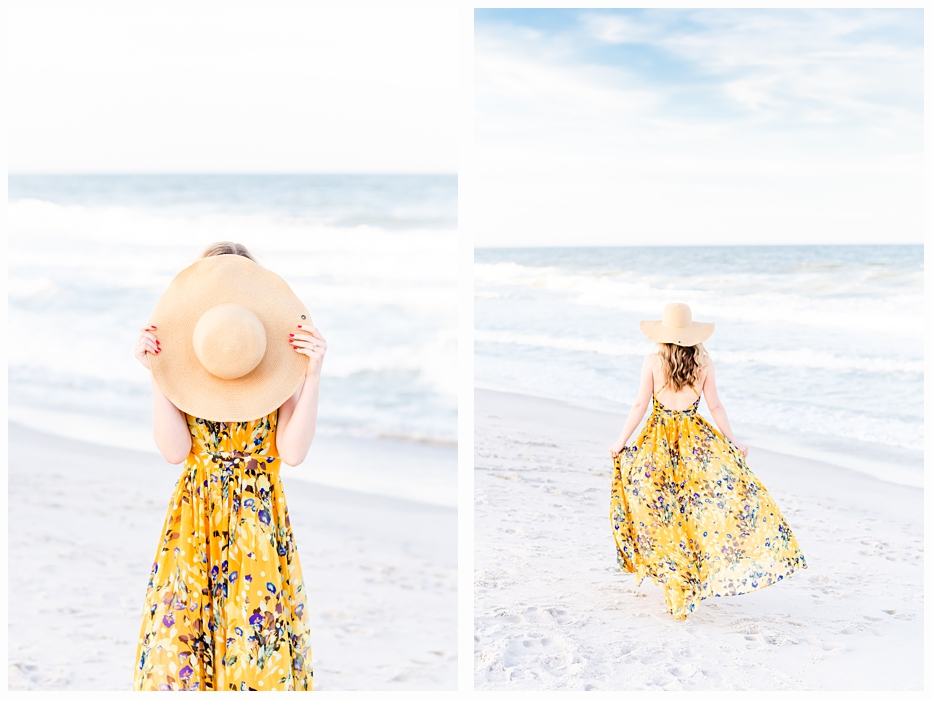 pretty woman dancing on the beach in a floral yellow dress wearing a straw hat