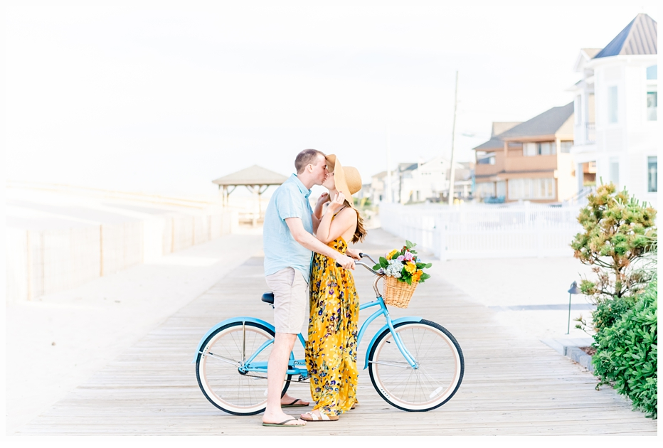 engaged man and woman on a pretty beach bicycle kissing