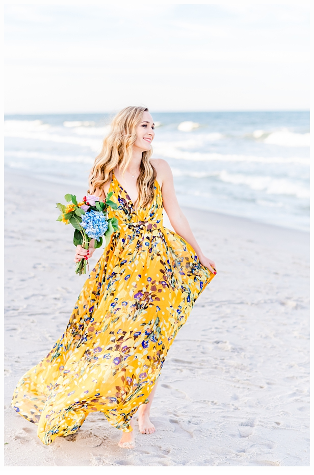 young woman carrying pretty bouquet on the beach with a yellow print dress