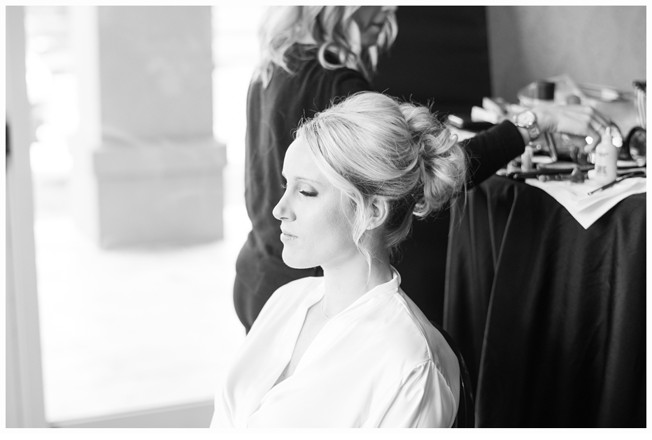 bride getting hair and makeup done on wedding day