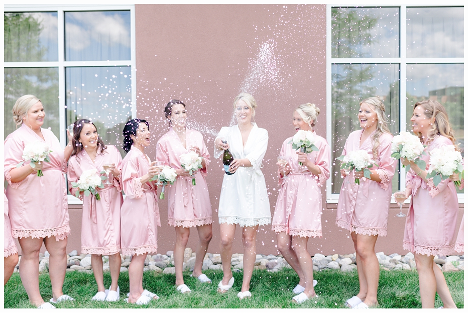 bride and bridemaids in pink silk robes popping champagne