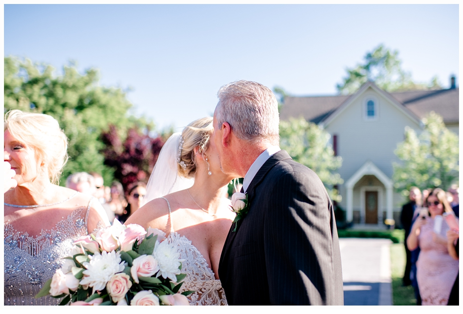 father giving bride away to groom at the altar