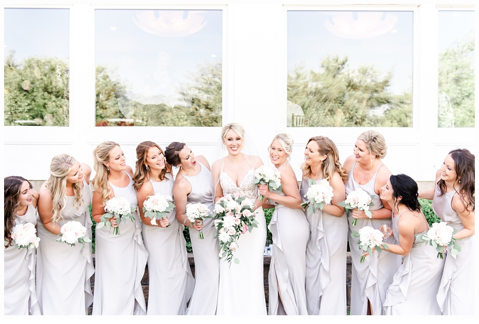 bride and bridesmaids laughing together wearing pretty grey dresses