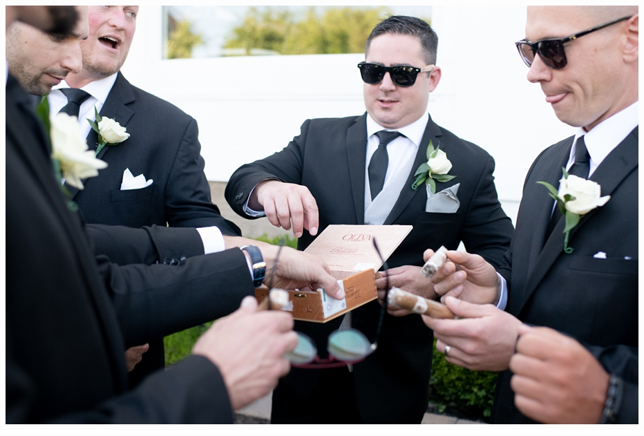 groom and groomsmen sharing a box of cigars