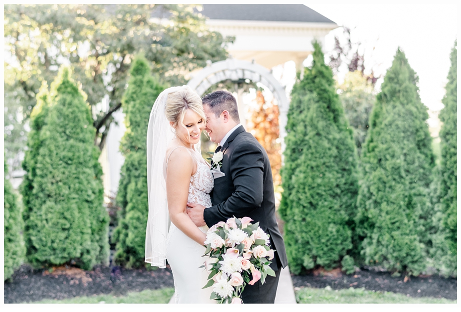 bride and groom standing in front of an arch for wedding portraits