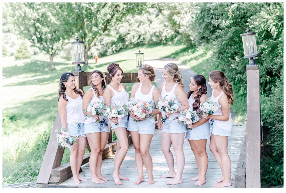 bride and bridesmaids carrying pretty bouquet on a bridge