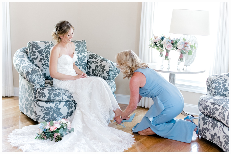 mother helping bride on with her wedding shoes