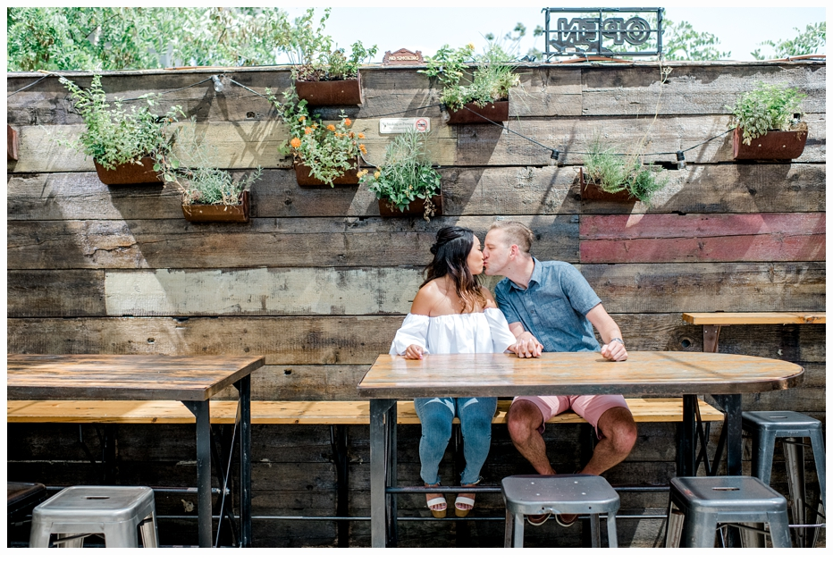 engaged couple kissing at a restaurant