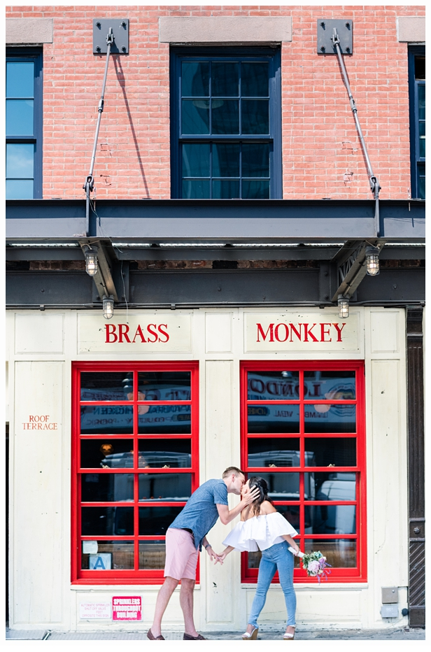 engaged couple in front of the brass monkey holding hands