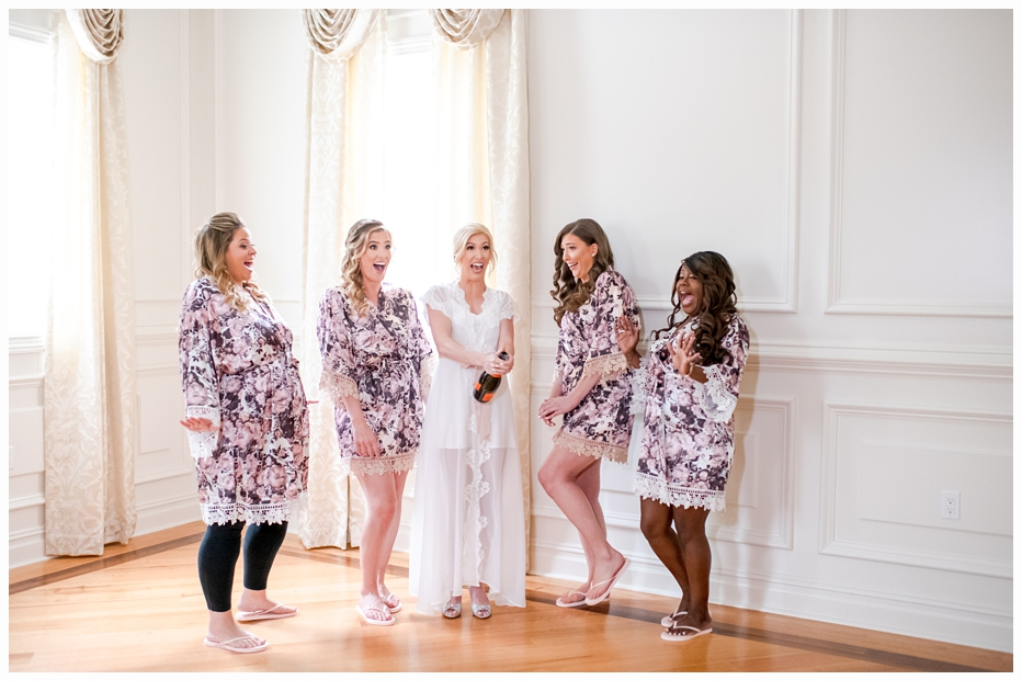 bride and bridesmaids in floral robes having a champagne toast