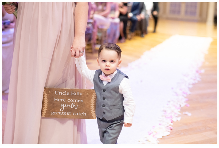 ringbearer carrying sign at wedding