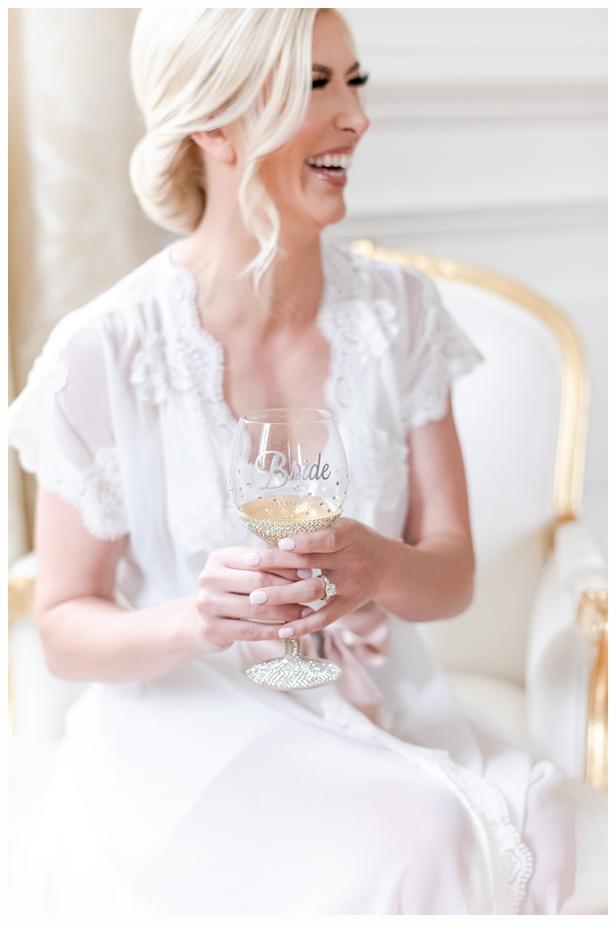 bride in pretty white robe drinking champagne